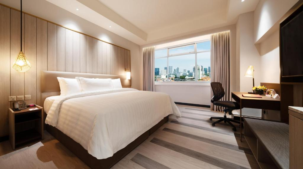A bed or beds in a room at PARKROYAL on Kitchener Road