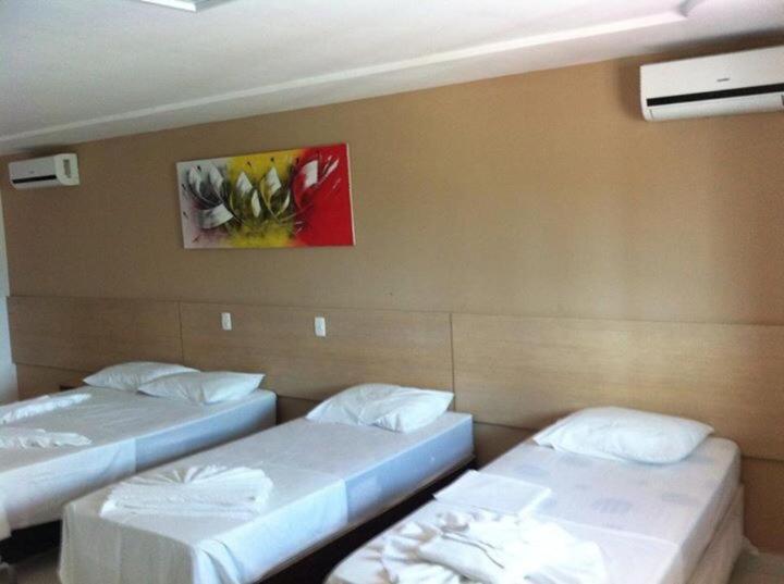 A bed or beds in a room at Pousada Veraneio Ponta Negra