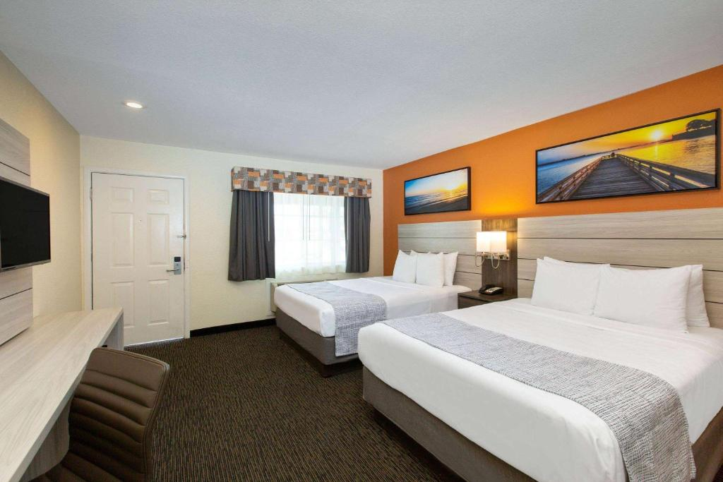 A bed or beds in a room at Days Inn by Wyndham Monterey-Fisherman's Wharf Aquarium