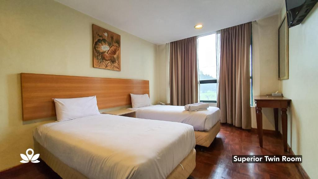 A bed or beds in a room at SCC Hotel