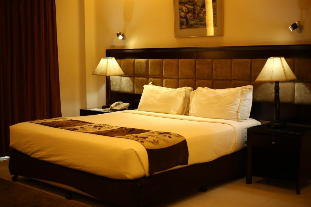 A bed or beds in a room at THE AVENUE HOTEL & SUITES