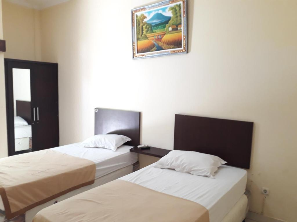 A bed or beds in a room at Sari Agung Kuta