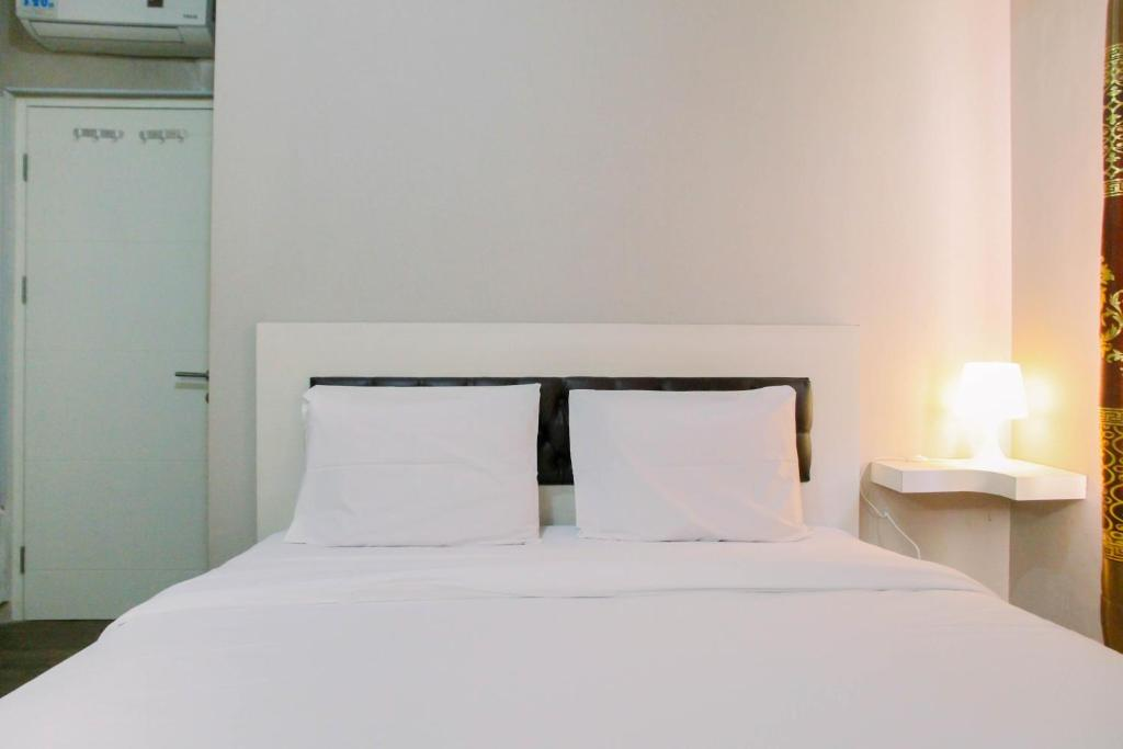 A bed or beds in a room at Modern Furnished 3BR at Springlake Summarecon Bekasi Apartment By Travelio
