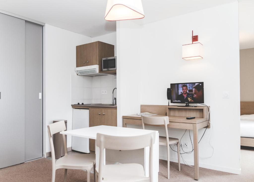 A television and/or entertainment center at Terres de France - Appart'Hotel Quimper Bretagne