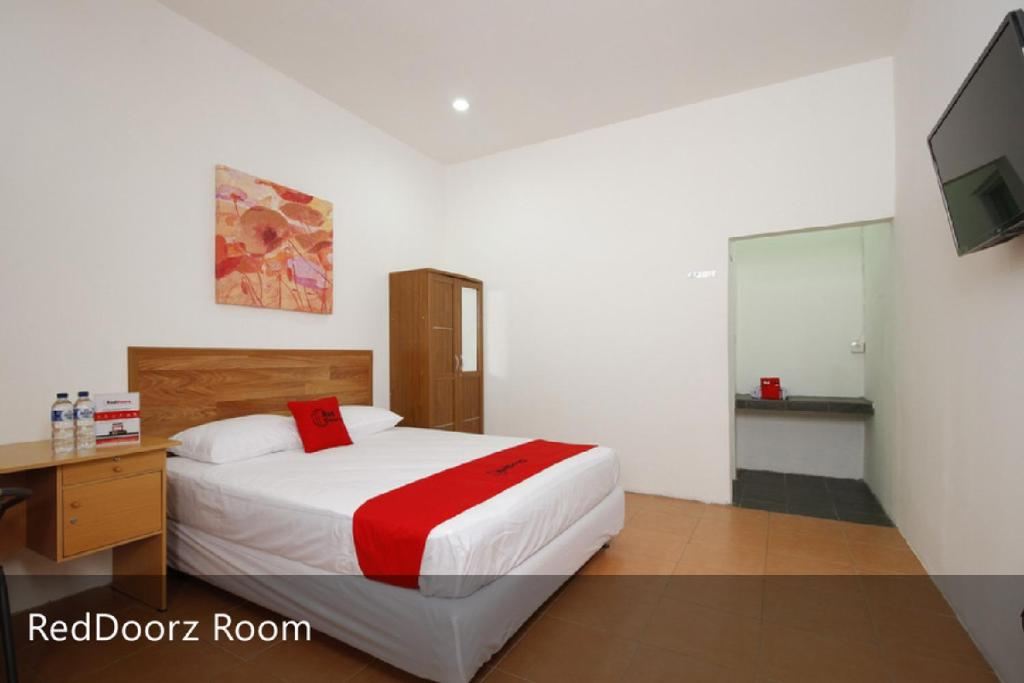 A bed or beds in a room at RedDoorz Plus near Plaza Indonesia