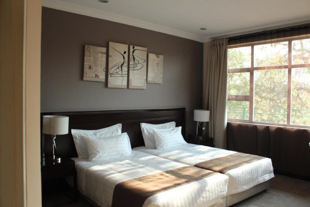 A bed or beds in a room at MalVille Boutique Hotel