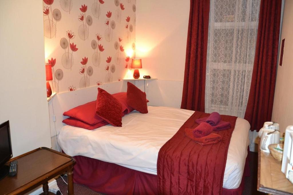 A bed or beds in a room at Chiswick Lodge Hotel