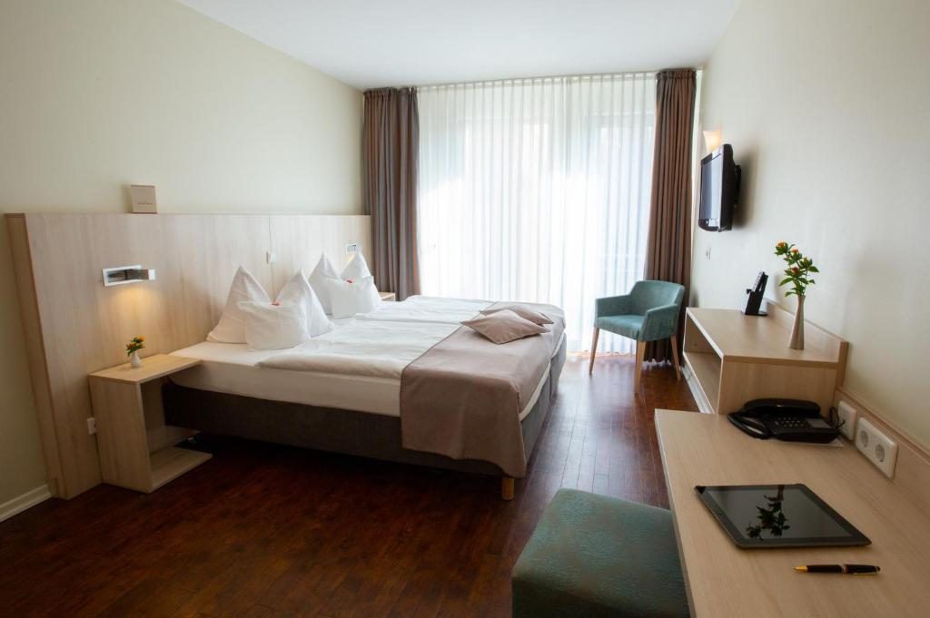 A bed or beds in a room at Stadthaushotel Hamburg - Inklusionshotel