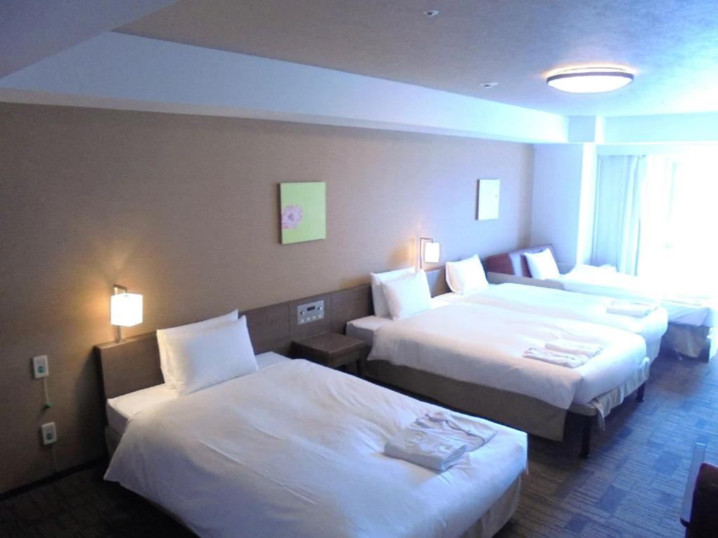A bed or beds in a room at Daiwa Roynet Hotel Naha Omoromachi