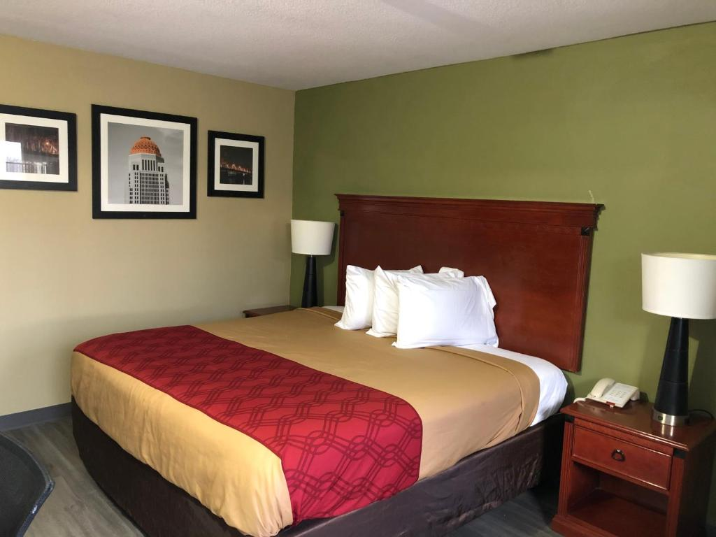 A bed or beds in a room at Deluxe Inn miami,ok