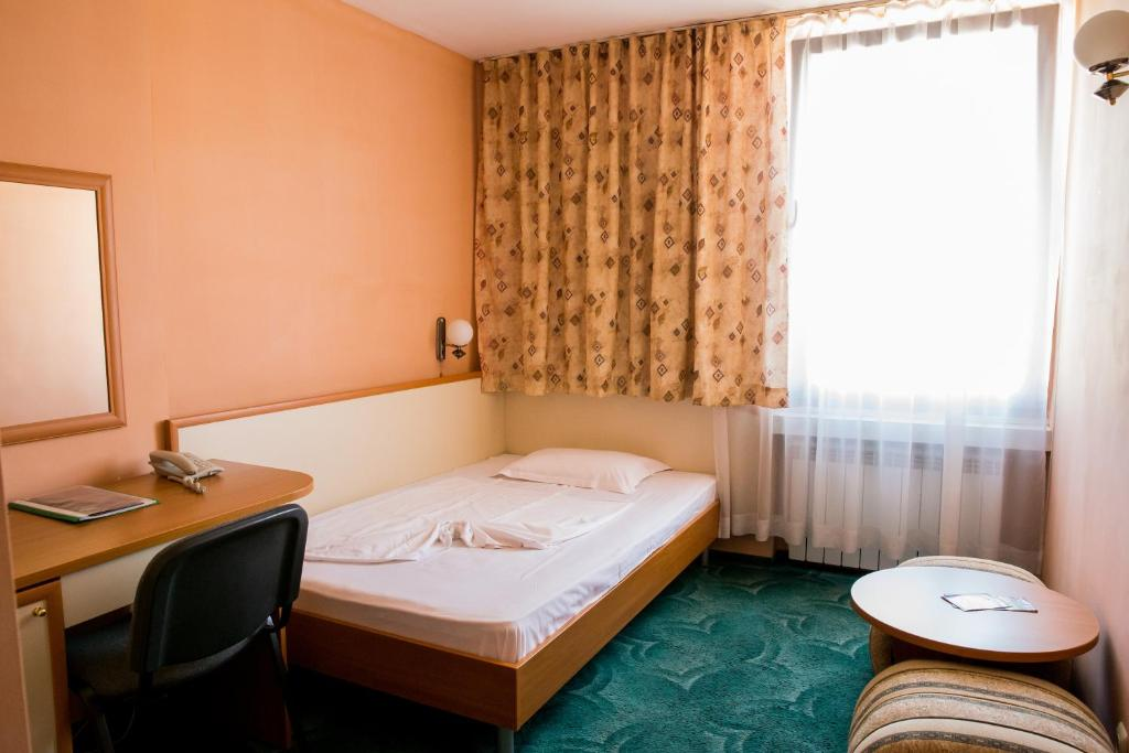 A bed or beds in a room at Struma Hotel