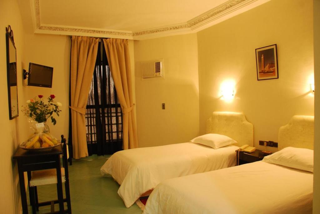 A bed or beds in a room at Hotel Nouzha