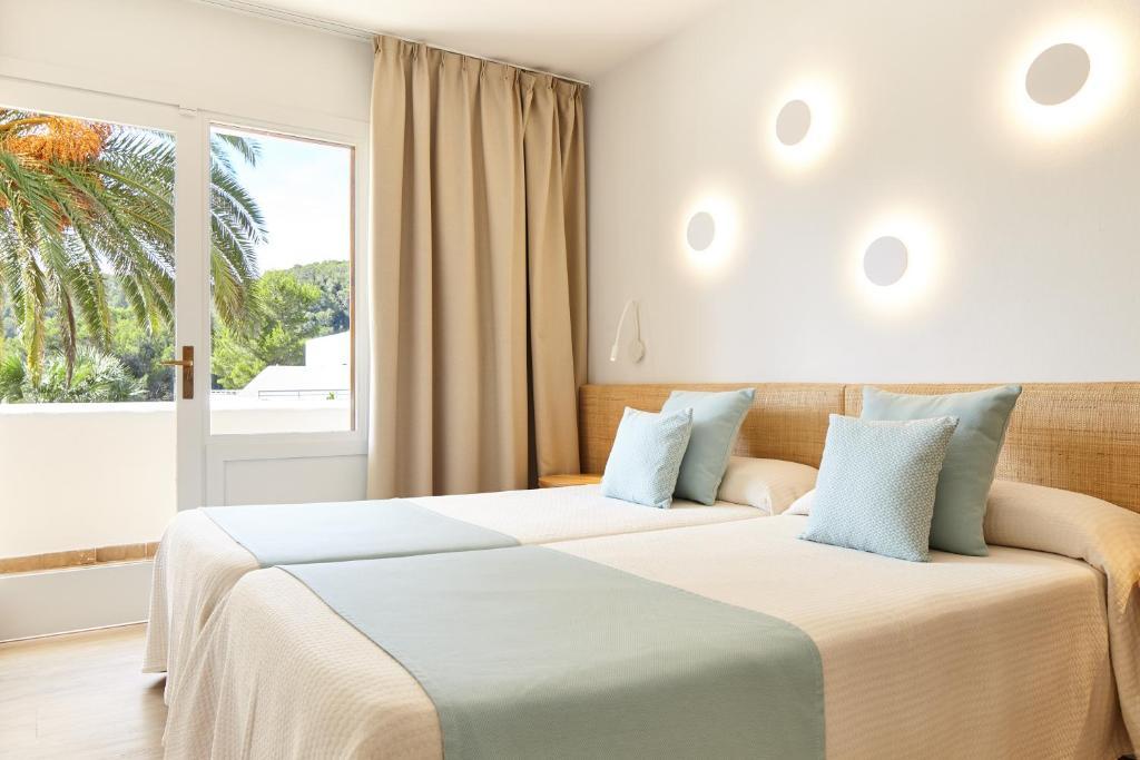 A bed or beds in a room at San Miguel Park / Esmeralda Mar