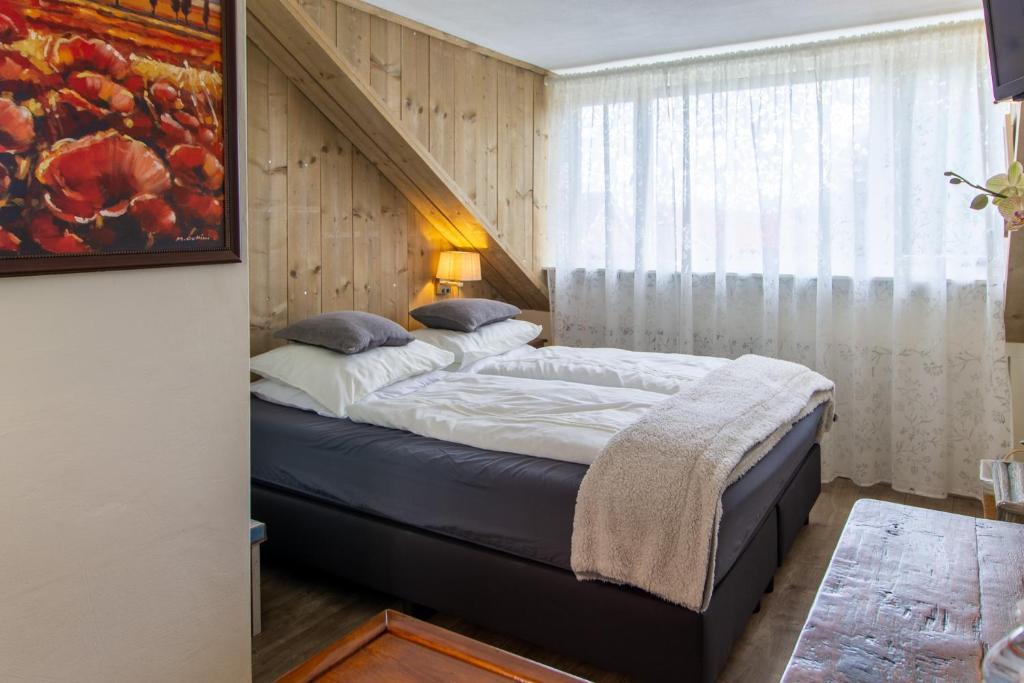 A bed or beds in a room at B&B Aan het Park Eindhoven