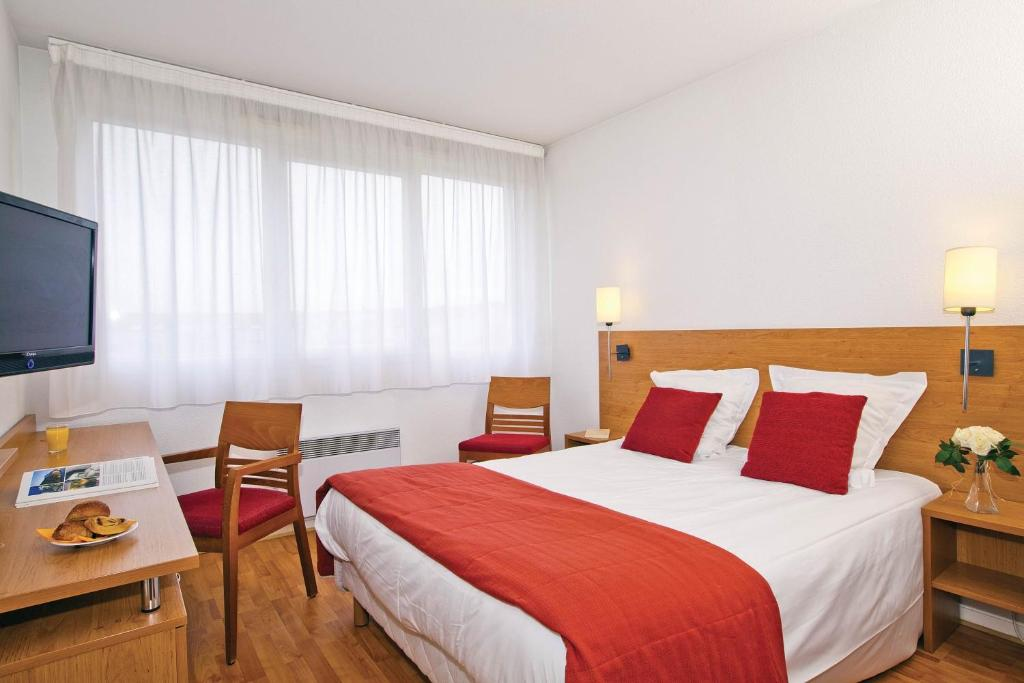 Кровать или кровати в номере Séjours & Affaires Lyon Saint-Nicolas