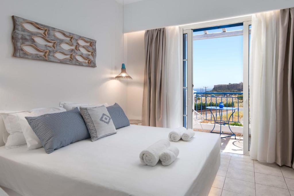Säng eller sängar i ett rum på 'Lindian Myth' Sea View Studios