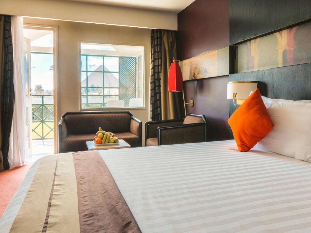 سرير أو أسرّة في غرفة في فندق ميركيور سفينكس القاهرة