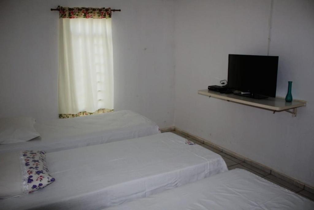 Cama ou camas em um quarto em Pousada Paraíso da Serra