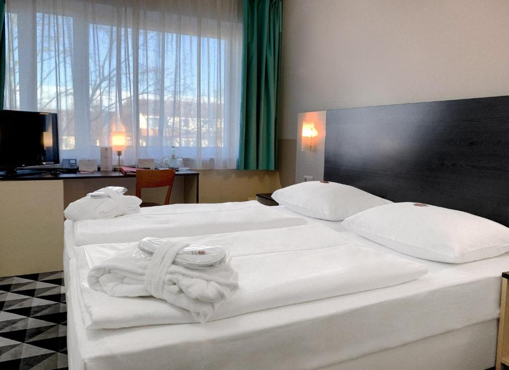 A bed or beds in a room at AZIMUT Hotel City South Berlin