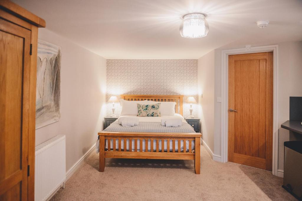 A bed or beds in a room at Home Farm & Lodge