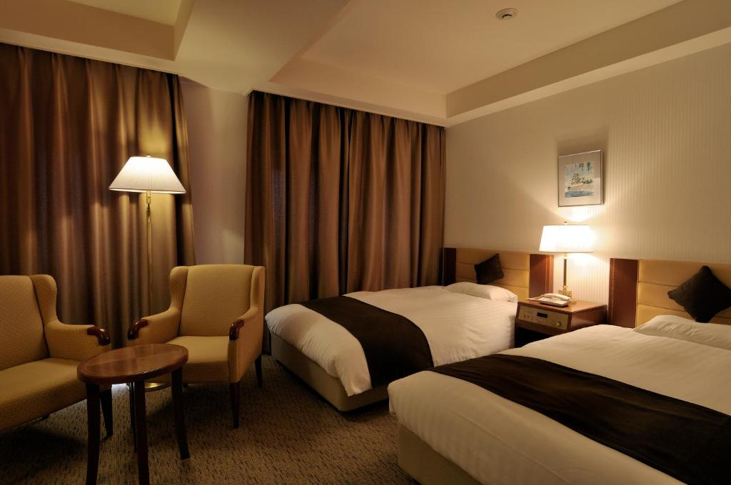 A bed or beds in a room at Hotel Grand Terrace Toyama