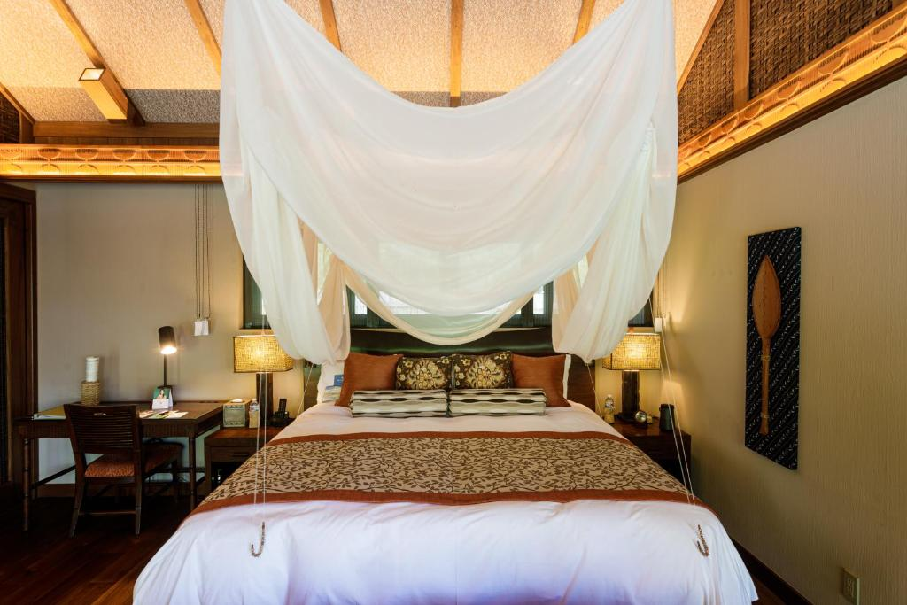 A bed or beds in a room at Palau Pacific Resort