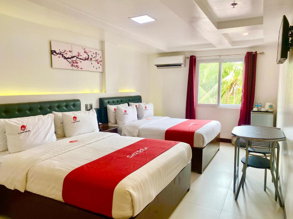 A bed or beds in a room at IL Mare Sakura Resort Boracay
