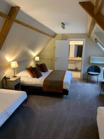 A bed or beds in a room at Hotel Ter Duinen
