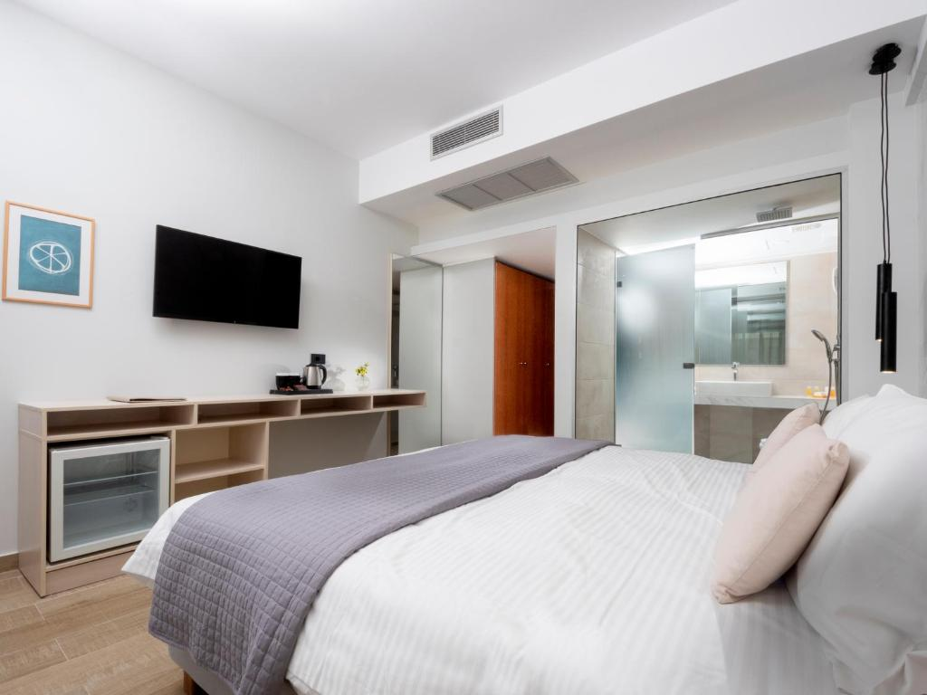 A bed or beds in a room at Athena Hotel