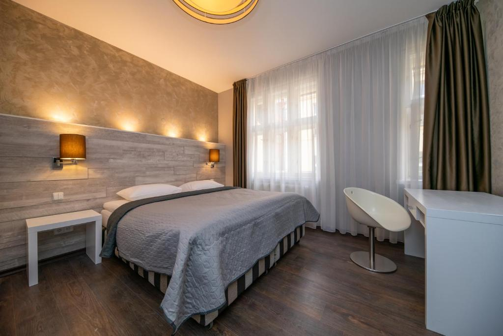 A bed or beds in a room at Emporio Prague Apartments