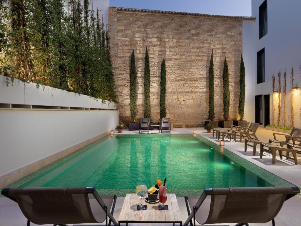 The swimming pool at or near H10 Palacio Colomera