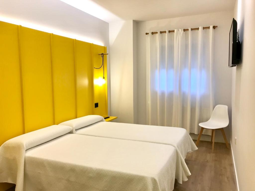 A bed or beds in a room at Albergue O Burgo