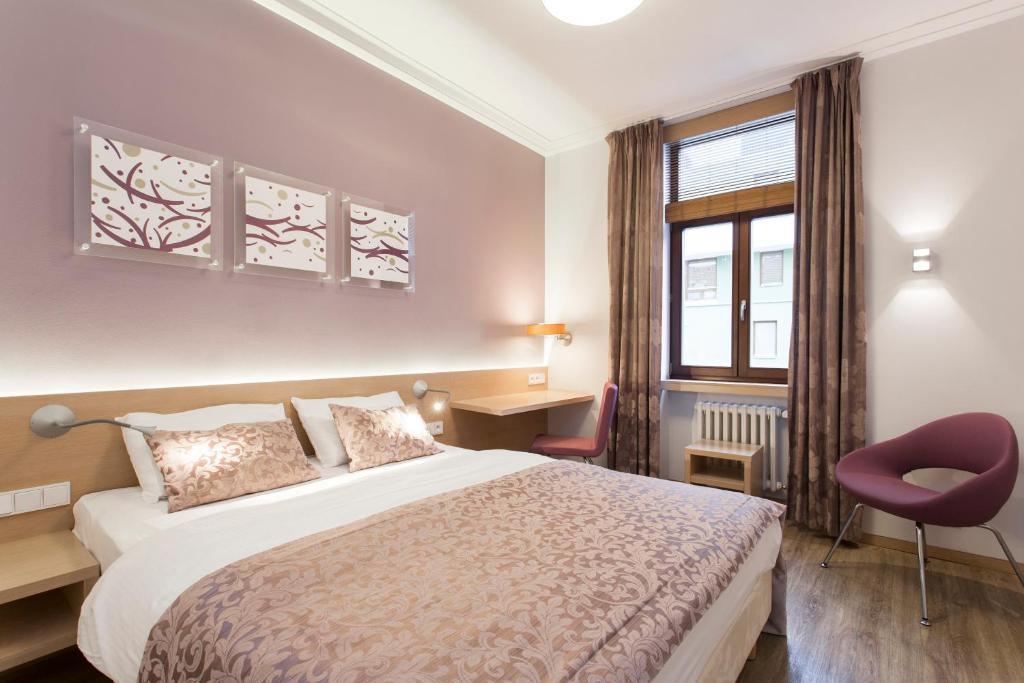 Postel nebo postele na pokoji v ubytování Hotel Carol