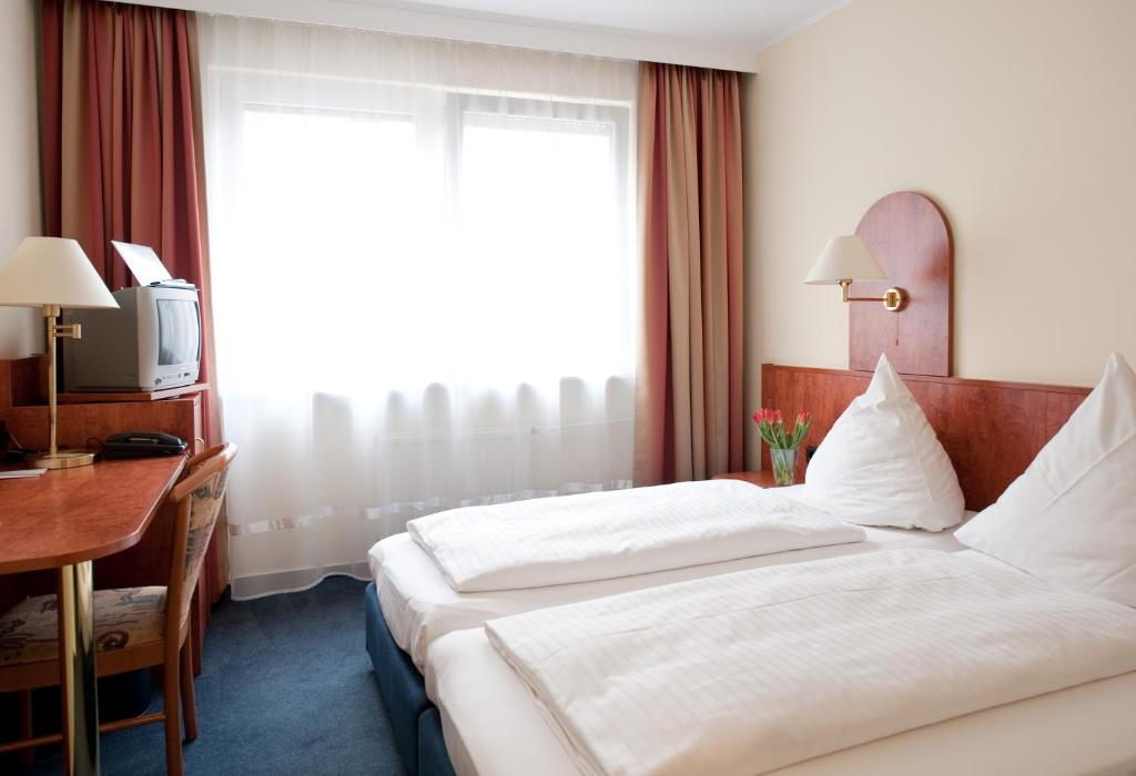 A bed or beds in a room at Falk Hotel