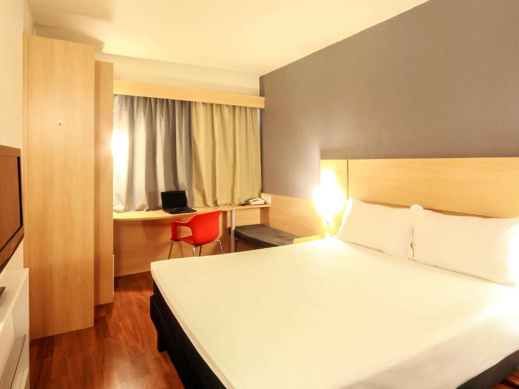 A bed or beds in a room at ibis Joinville