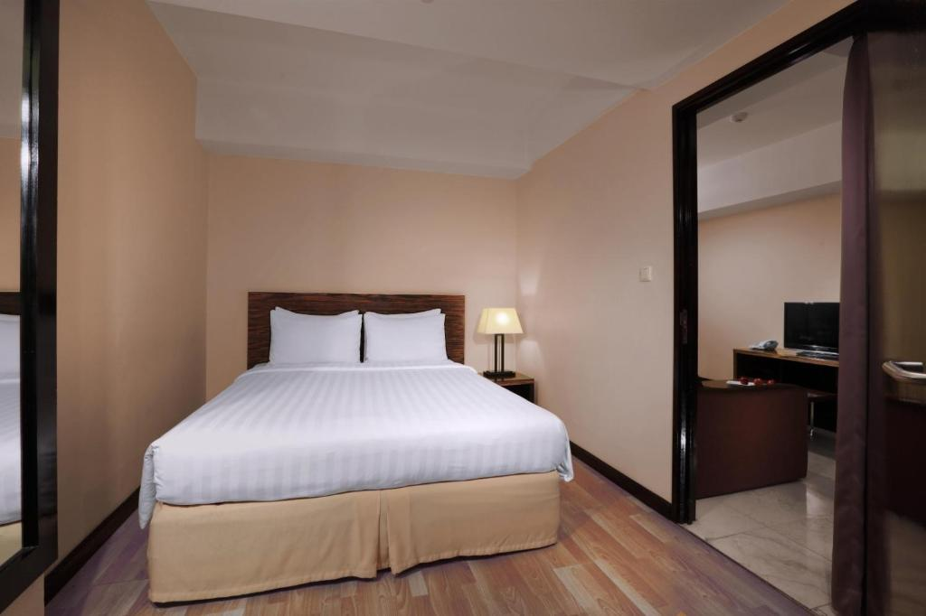 A bed or beds in a room at Grand Dafam Braga Bandung