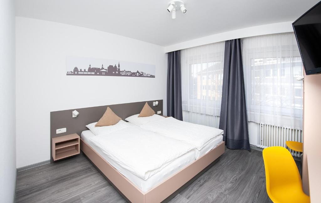 A bed or beds in a room at Hotel Stadtnah
