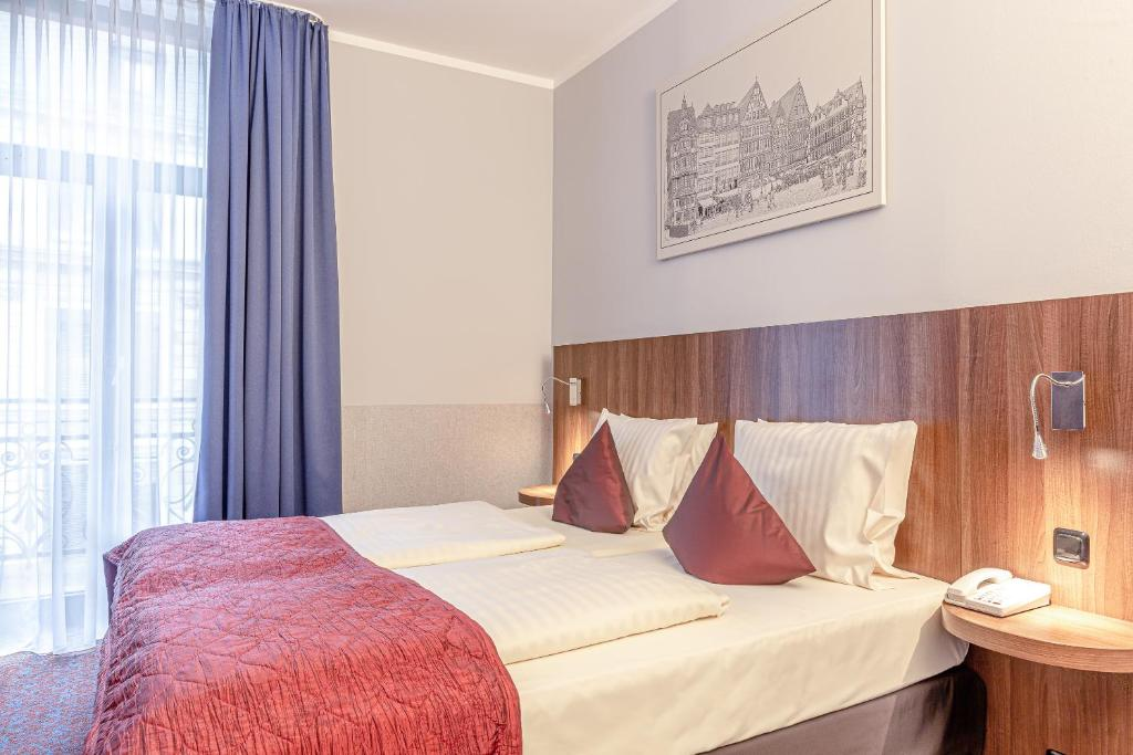 A bed or beds in a room at ALL-INN Hotel Frankfurt