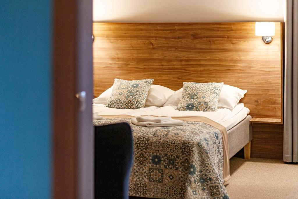 A bed or beds in a room at Stay Vilnius Family Hotel