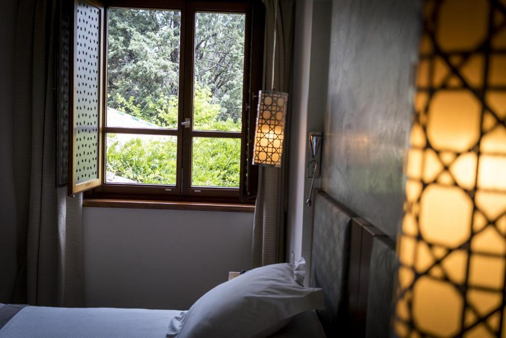 A bed or beds in a room at Parador de Granada