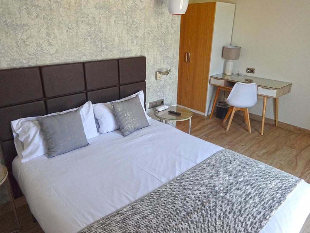 A bed or beds in a room at Hotel Lloret Ramblas