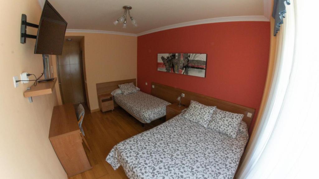 A bed or beds in a room at Hostal Santiago 2