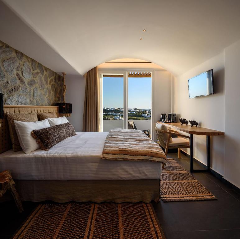 A bed or beds in a room at Vrachos Suites Mykonos