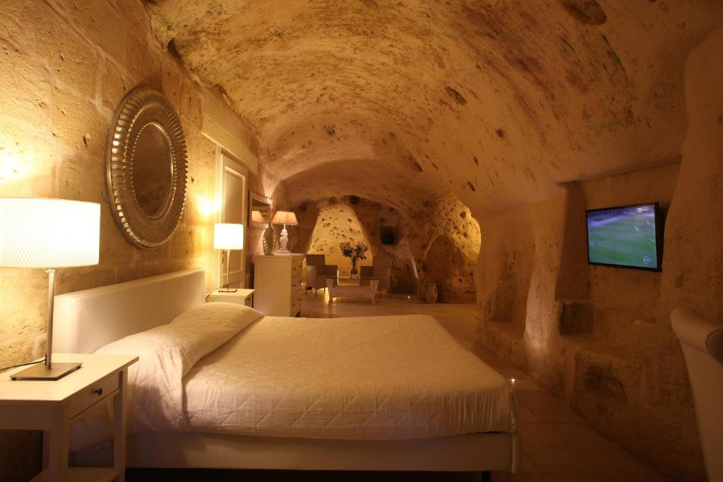 A bed or beds in a room at Caveoso Hotel