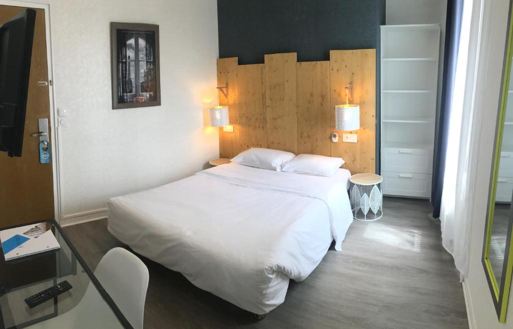 A bed or beds in a room at Hôtel du Maine