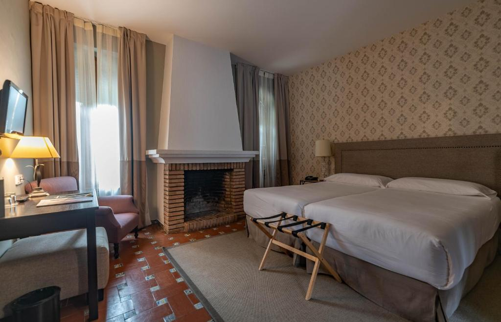 A bed or beds in a room at La Almoraima Hotel