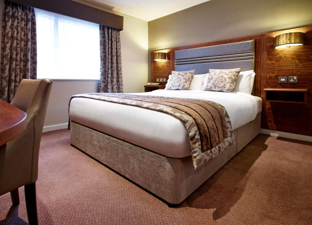 A bed or beds in a room at The Briar Court Hotel