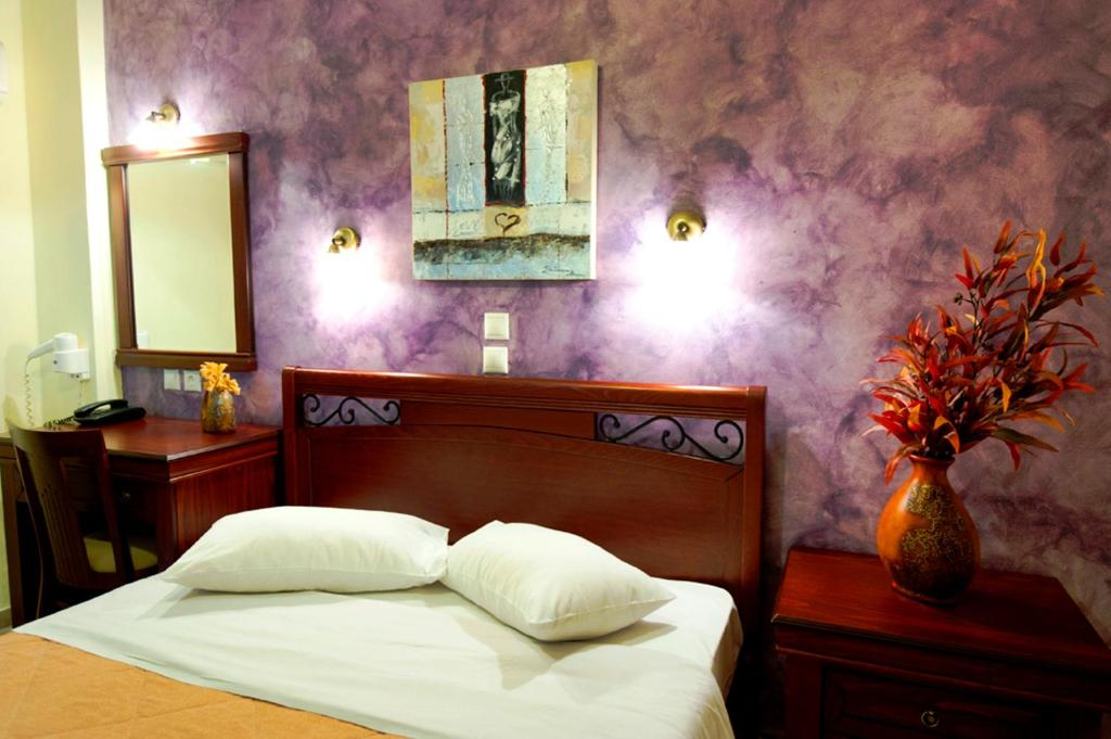 A bed or beds in a room at Pergamos Hotel
