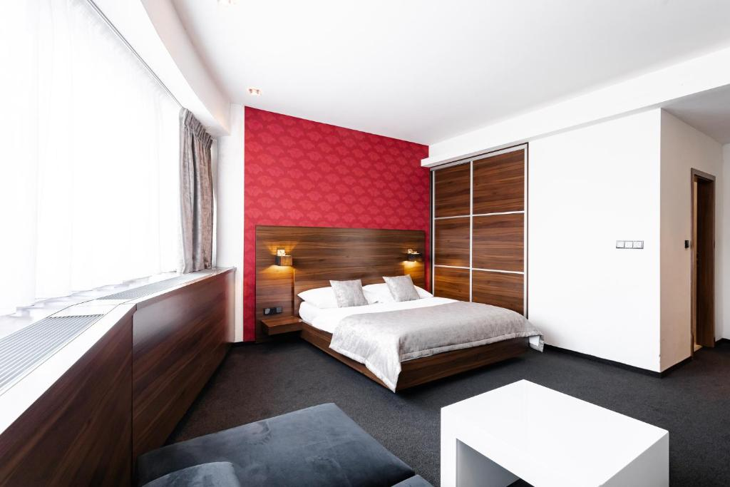 A bed or beds in a room at Tempus Club Garni Hotel