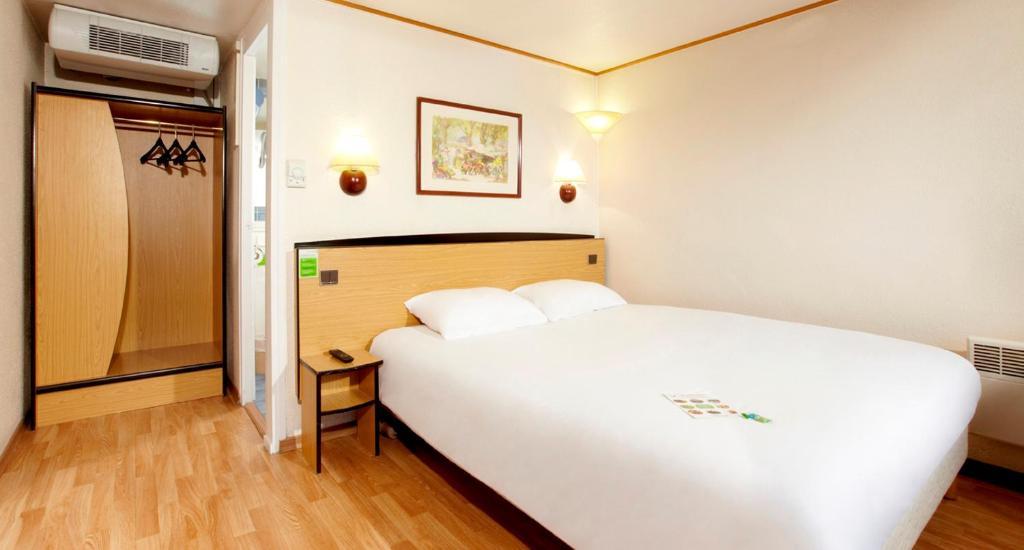 A bed or beds in a room at Campanile La Ferté-Bernard
